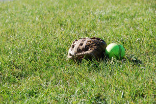 baseball glove and ball in field